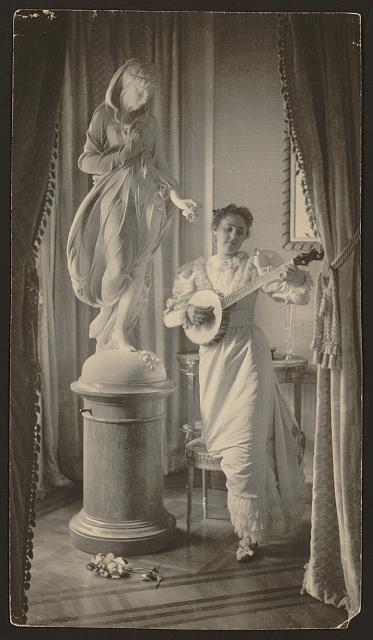 "[""Miss Apperson"" playing banjo beside statue of ""Flora"" in niche of Sen. George Hearst's residence, Washington, D.C.]"
