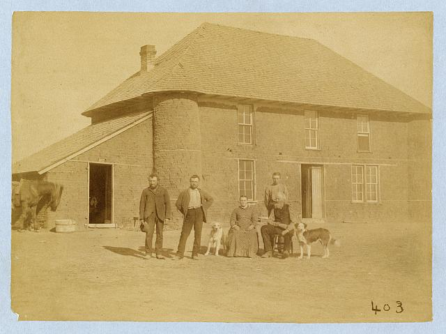[Isadore Haumont and family in front of two-story sod house on French Table north of Broken Bow, Custer County, Nebraska]