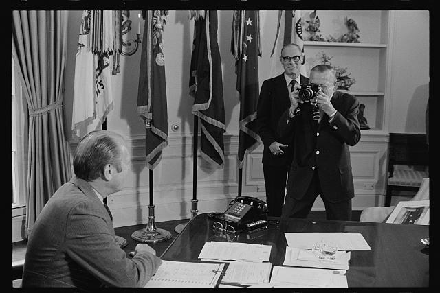 [President Gerald Ford being photographed by Buck May in the Oval Office of the White House, Washington, D.C.]