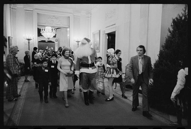 [First Lady Betty Ford, Santa Claus, and clowns lead a procession of Diplomatic Corps children at a White House Christmas party, Washington, D.C.]