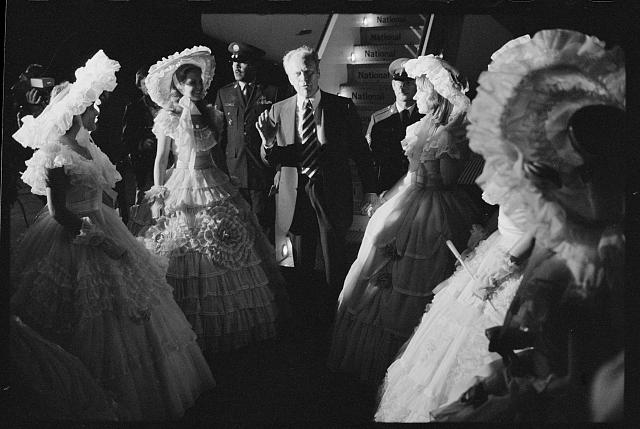 [President Gerald Ford greets a group of young women dressed as Southern belles at a campaign stop in the South]