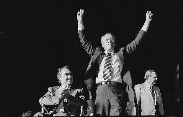 [President Gerald Ford makes a victory sign as George Wallace applauds at a campaign stop in the South]