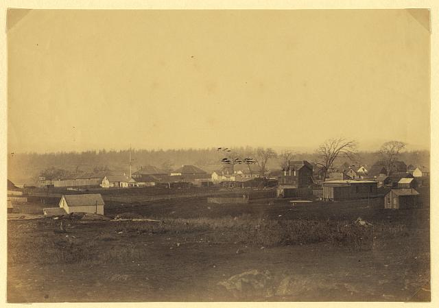 [Community adjacent to the fur trading post at Fort Victoria on Vancouver Island, British Columbia, showing cluster of buildings and possibly the fort just left of center]