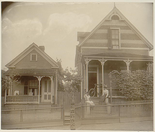 [African American boy seated on porch of house, another African American boy standing with bicycle on porch of another house, with two young African American women on steps, Georgia]