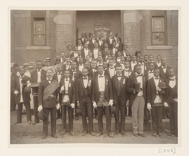 "[African American men posed at entrance to building, some with derbys and top hats, and banner labeled ""Waiters Union"" in Georgia]"