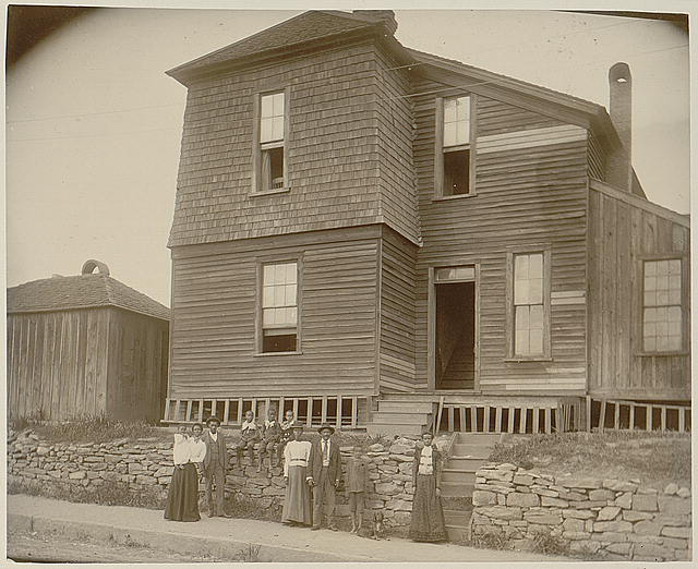 [African Americans standing on sidewalk in front of house in Georgia]