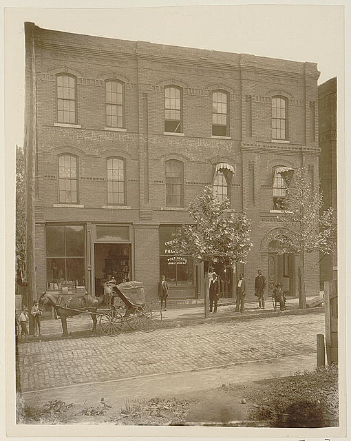 "[African Americans standing outside brick building ""Frien[dship] Phar[macy]"" and ""Post Office"", with horse-drawn carriage in street]"