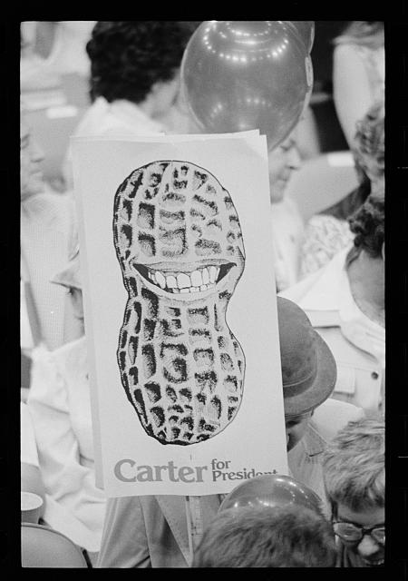 "[Jimmy Carter supporter holding ""Carter for President"" sign showing a peanut shell with a toothy grin at the Democratic National Convention, New York City]"