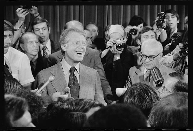 [President Jimmy Carter at a press conference, surrounded by journalists]