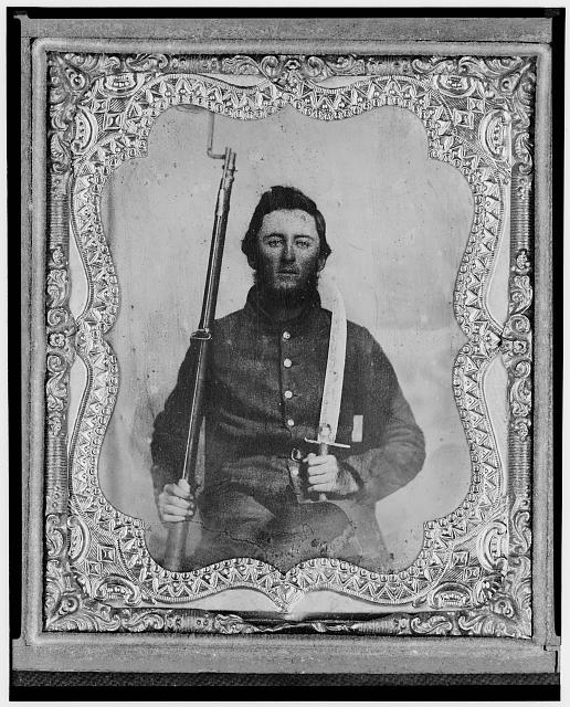 [Thomas Kitchen, Pvt., Georgia regiment, C.S.A., three-quarter length portrait, seated holding bayonet and rifle, facing front]