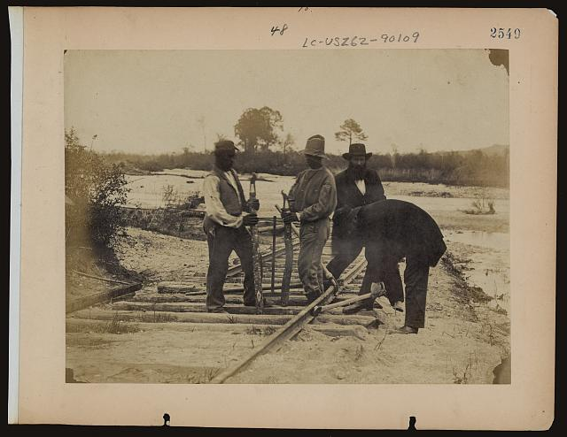 [Military railroad operations in northern Virginia: men using levers for loosening rails]