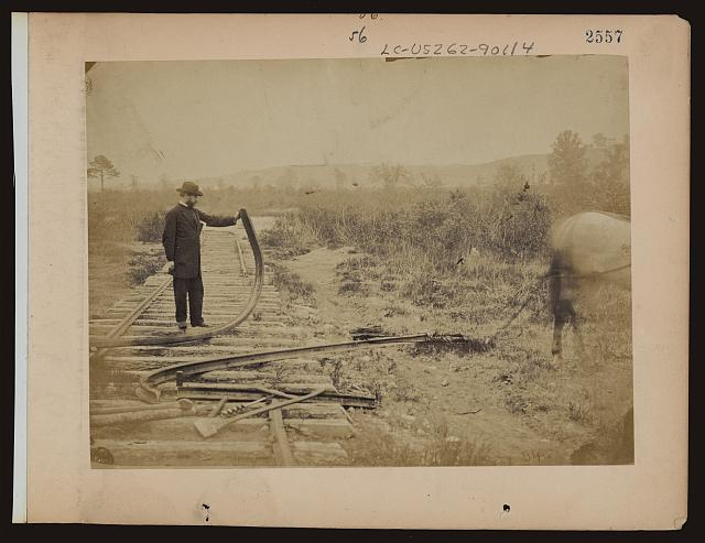 [Military railroad operations in northern Virginia: man standing on railroad tracks holding twisted rail]