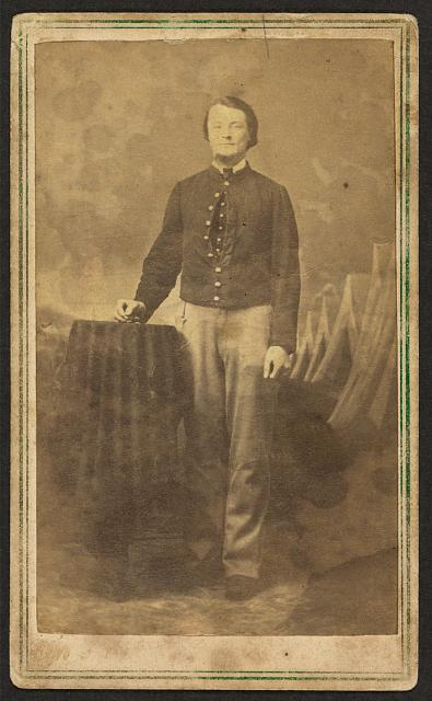 [Full-length portrait of unidentified civil war soldier standing next to a table]