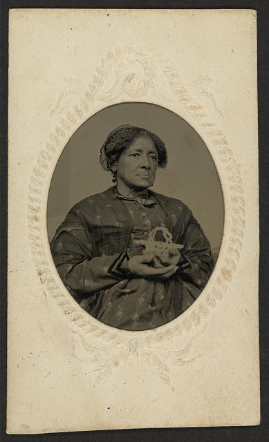 [African American woman, half-length portrait, seated, holding a basket]