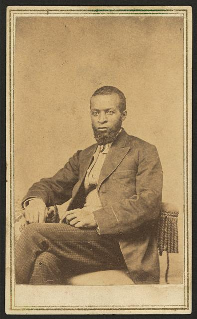 [Three-quarter-length portrait of an African American man, seated, facing left]