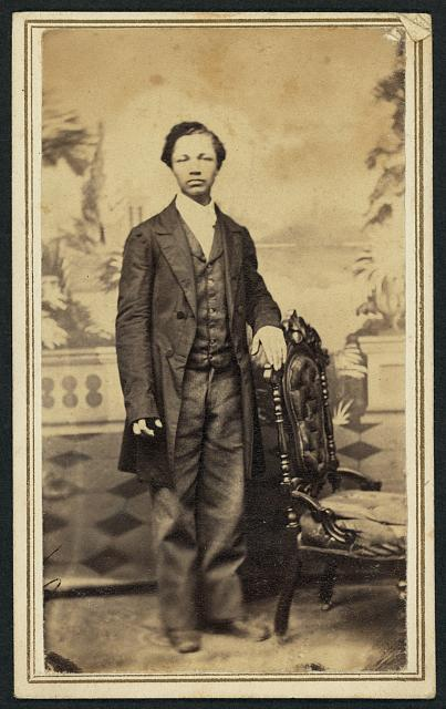 [Full-length portrait of an unidentified African American man standing beside a chair]