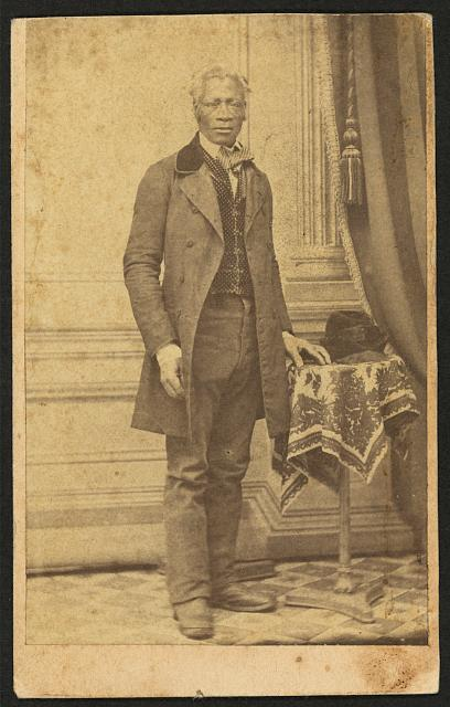 [Full-length portrait of unidentified African American man in suit, standing next to a table]
