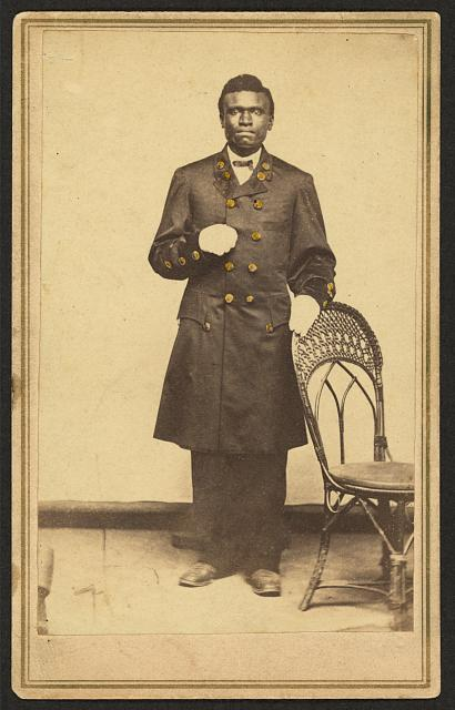 [Full-length portrait of an African American man wearing long coat and gloves, standing, facing front]