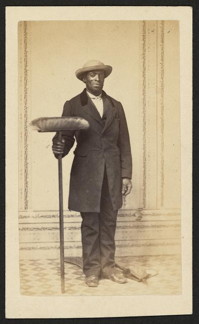 [Full-length portrait of an African American man holding a broom]