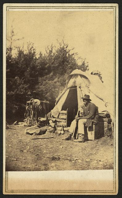 [African American man, sitting outside a military camp tent]