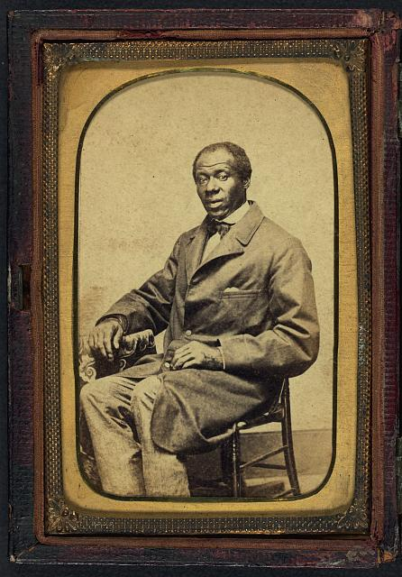 [Unidentified African American man, full-length portrait, seated, facing slightly left]