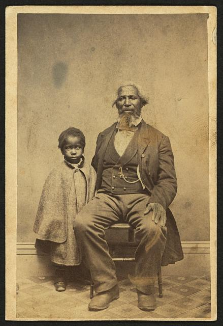 [African American man and child, full-length portrait, facing front]