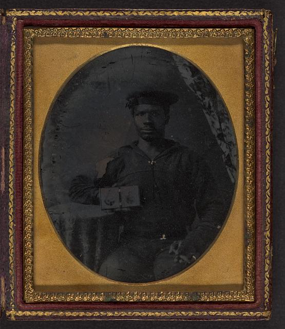 [Sailor with cigar in hand holding a double case image of confederate soldiers]