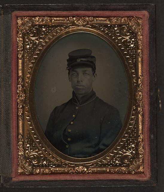 [Unidentified Union soldier in frock coat, private, kepi, 3rd-5th buttons open on coat]