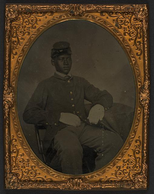 [Seated black soldier, frock coat, gloves, kepi]