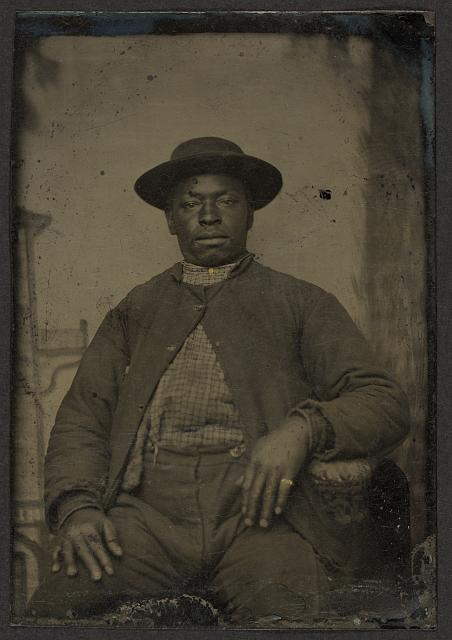 [Seated black man wearing four button sack, laborer, ring]