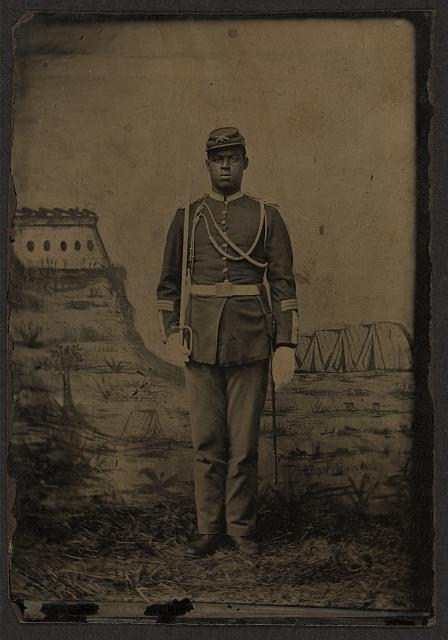 "[Black soldier, Indian war period, Infantry, Co. D with shoulder knots, holding noncom sword, wearing aiguelette, crossed rifles with ""D"" on kepi, white gloves plus 3 service stripes (i.e. 15 years service)]"