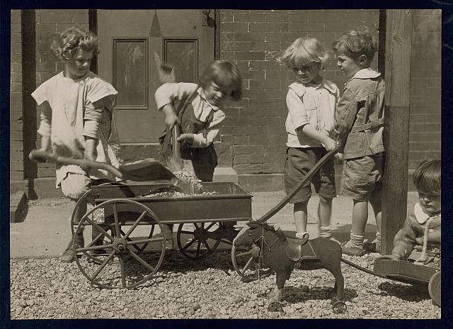 [Four young children loading rocks into a wagon while a smaller chid sits on the ground playing with his toy ponycart]