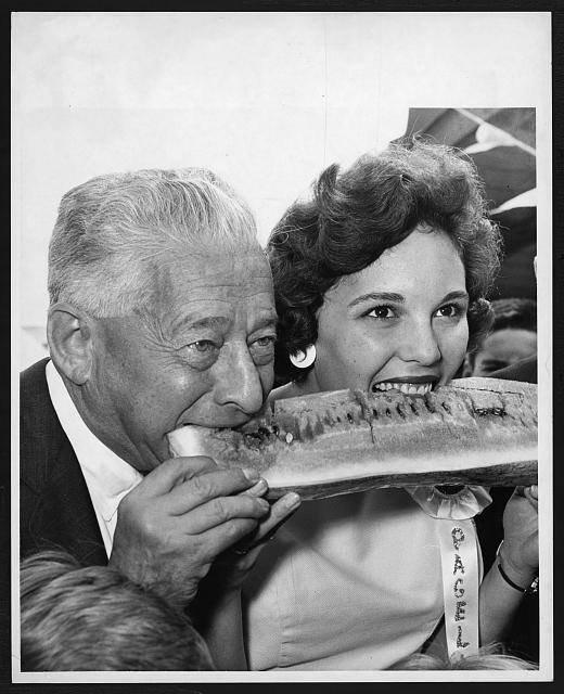 "[Mimi Fellers, ""Watermelon Queen"" from South Carolina and Abe Stark, New York City council president, biting into a watermelon at the Brooklyn Terminal Market]"