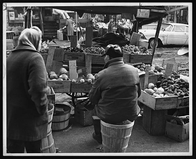 [Produce vendor, bundled up against the cold, sits on a bushel basket by his pushcart, Brooklyn, New York]