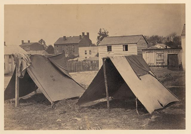 [Two small tents, with wood frame buildings in the background]