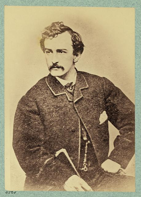 [John Wilkes Booth, half-length portrait, facing left and holding a cane]