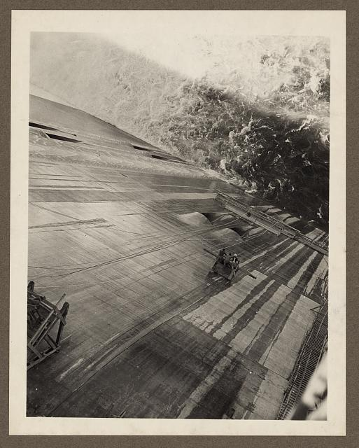 Grand Coulee Dam, Columbia Basin Reclamation Project, Wash. Looking down the face of the dam from the roadway on top. Men are riding a skip to the area to be repaired