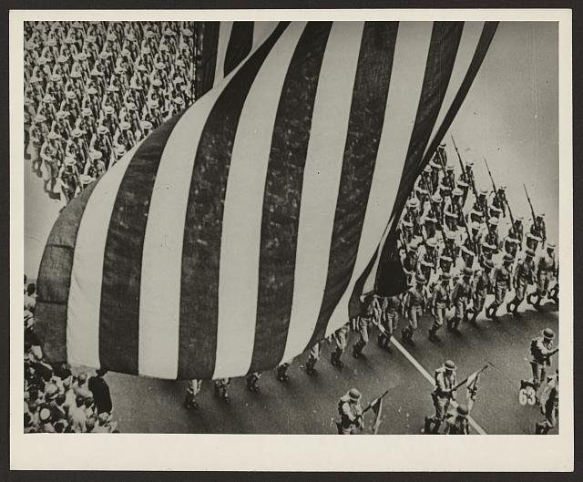 [View from above of soldiers marching, carrying rifles with bayonets fixed, with stripes portion of American flag above them]