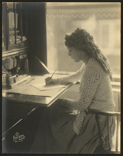 [Mary Pickford writing at a desk]