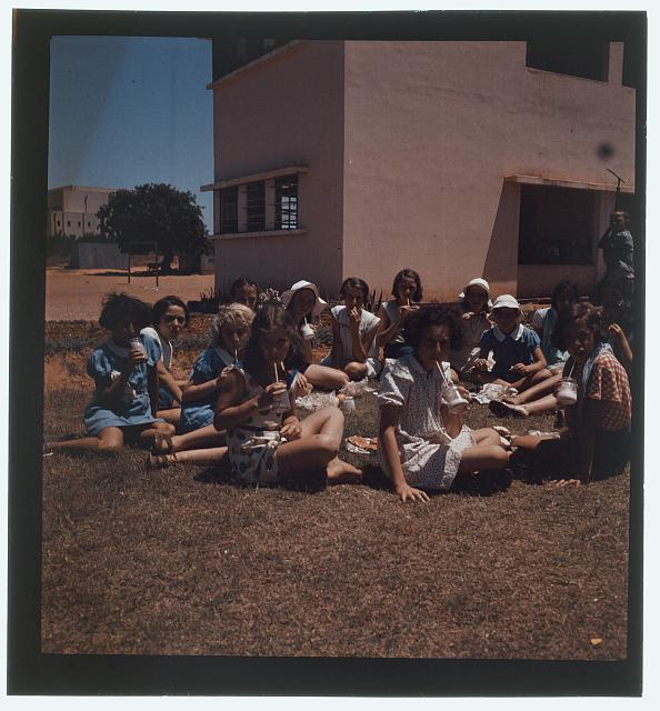 [Jewish? children seated on ground with food and drinks]