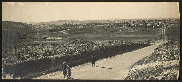 [Two Arab men and a woman walking down a road, Jerusalem in background]