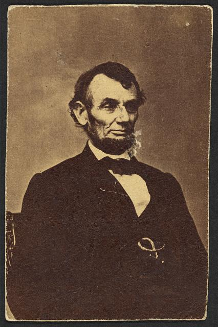 [Abraham Lincoln, three-quarter length portrait, seated, facing right; hair parted on Lincoln's right side]
