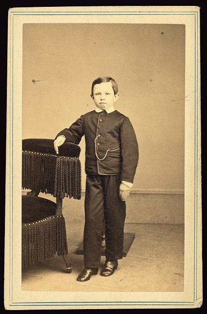 [Tad Lincoln, standing, leaning against a chair]