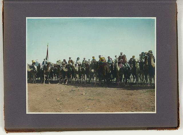 [Amir Abdullah's bodyguard on camels with red, green and white standard at far left]