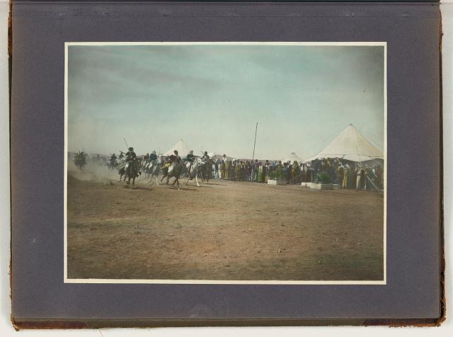 [Arab men racing horses while crowd looks on, tents in background]