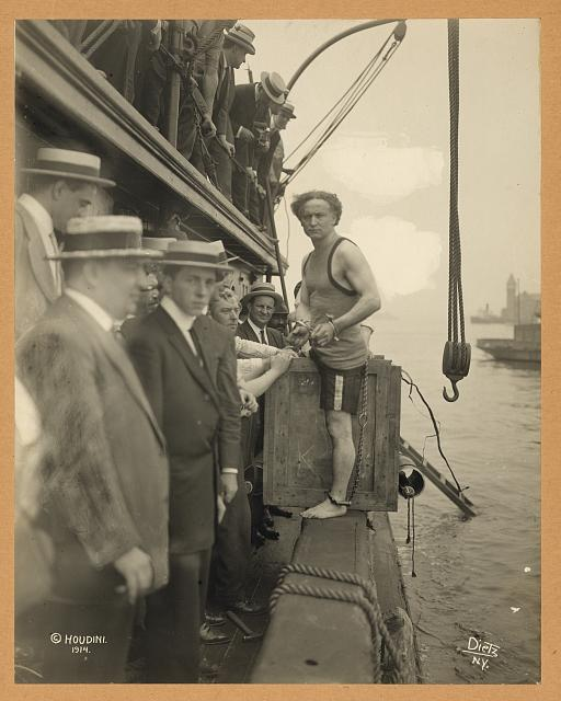 [Harry Houdini stepping into a crate that will be lowered into New York Harbor as part of an escape stunt on July 7, 1912]