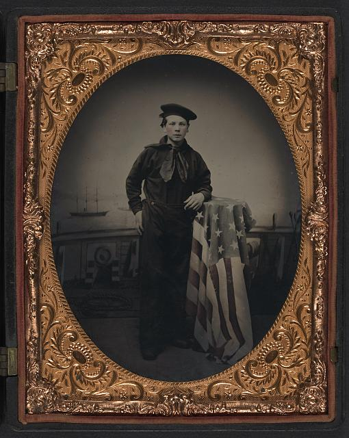 [Unidentified young sailor in Union uniform with American flag in front of backdrop showing naval scene]