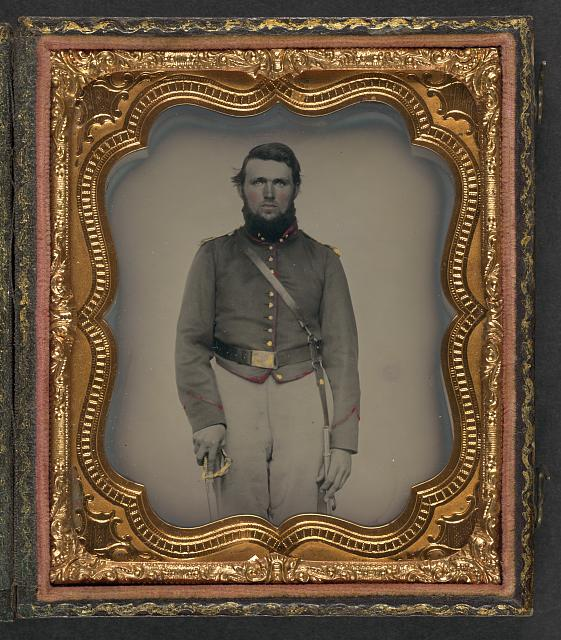 [Unidentified soldier in Union artillery uniform with red piping holding sword]