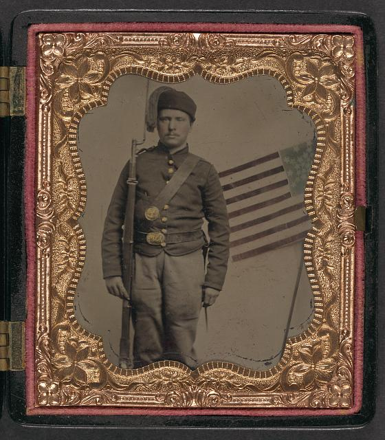 [Unidentified soldier in Union uniform with Zouave fez and bayoneted musket in front of painted backdrop showing American flag]