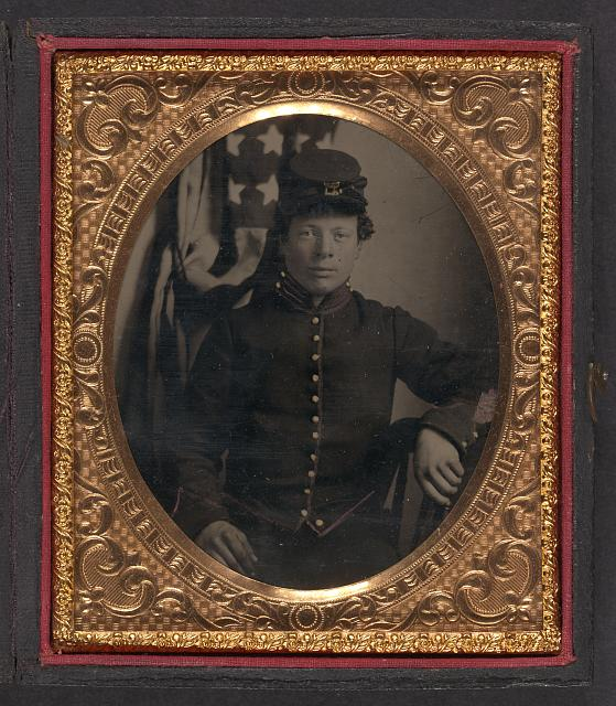 [Unidentified soldier in Union artillery uniform sitting in front of American flag]